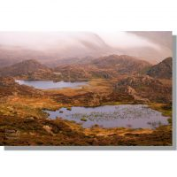 Tarns on Haystacks summit plateau during stormy red sunset