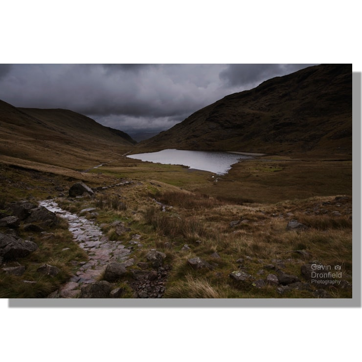 styhead pass footpath passes styhead tarn under dark ominous stormy skies at sunset