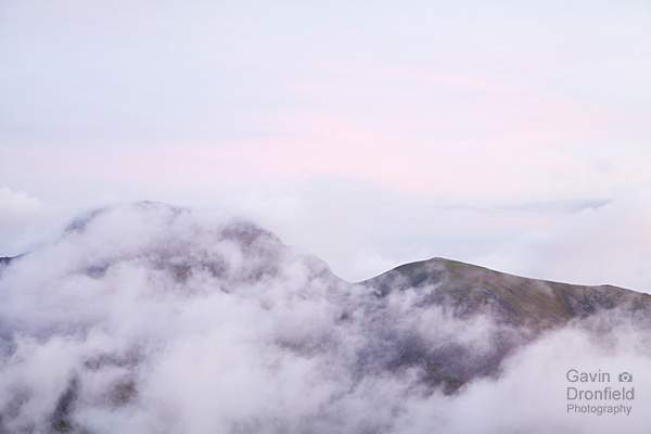 green gable appearing above dawn cloud while great gable hidden under pink tinged dawn skies