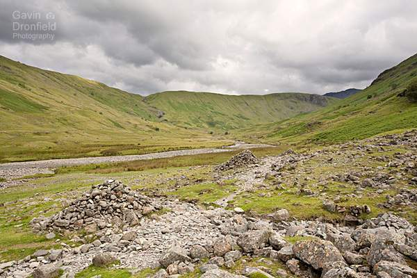 cairns lining the footpath in the remote green langstrath valley under cloudy skies