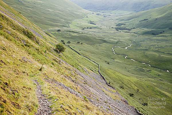 footpath from angle tarn descending into a shaded bannerdale valley above dry stone wall