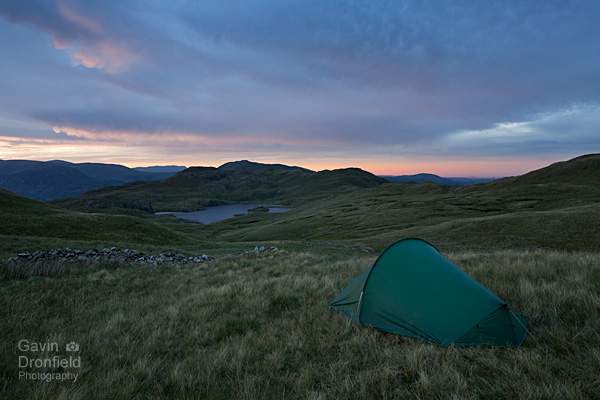 distant angle tarn during colourful sunset while wild camping at brock crags