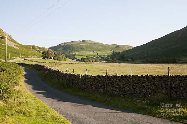 martindale country lane leading towards hallin fell under blue summer skies