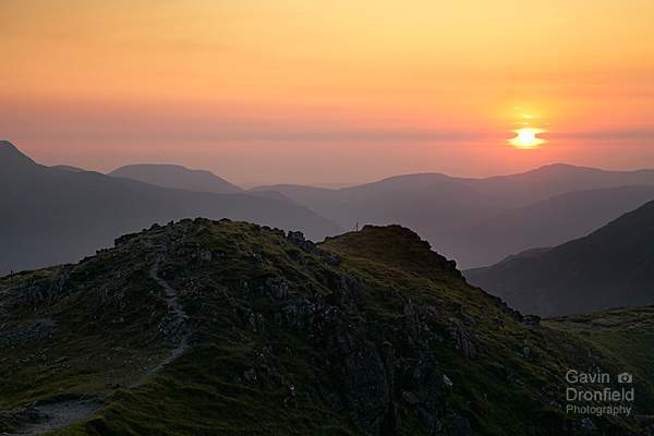 dale head summit ridge view of the setting sun over loweswater fell in summer