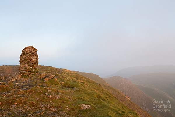 cairn on dale head in warm dawn light under light grey mist