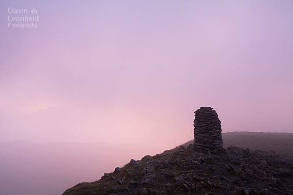 atmospheric pink tinged cloud swirling round silhouetted summit cairn on dale head at dawn