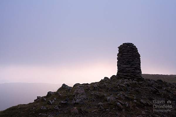 murky grey clouds over silhouetted dale head summit cairn
