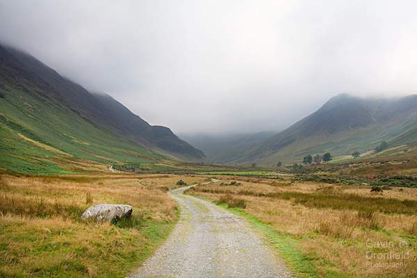 track towards newlands climbing hut with newlands fells under heavy cloud