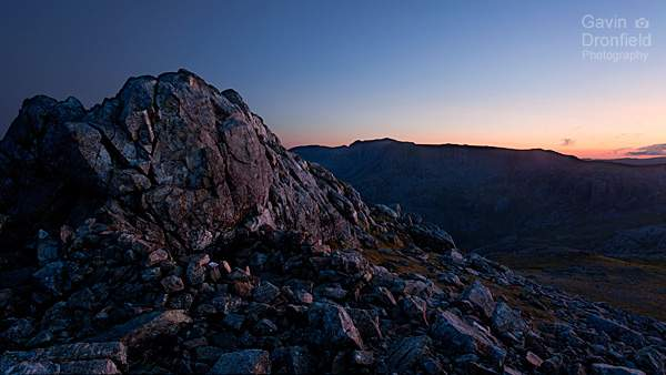 esk pike summit shelter with silhouetted scafell pike ridge background during clear orange summer sunset