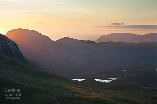 the gables – great gable and green gable – silhouetted over sprinkling tarn at summer during a dazzling red sunset