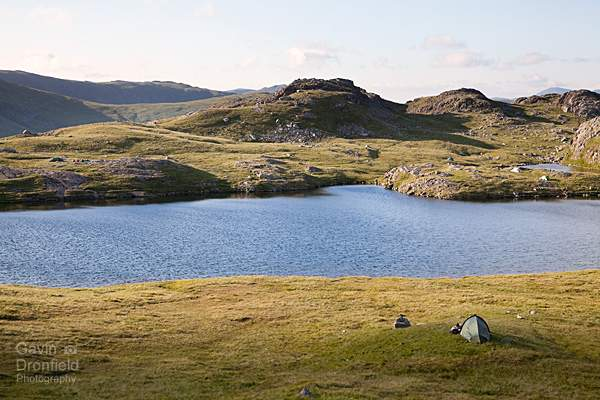 tents pitched around the shore of styhead tarn on a summer evening