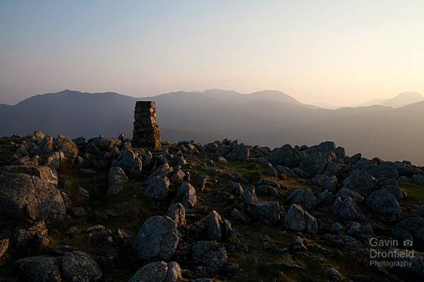 clear sunset from High Raise trig point looking towards bow fell, scafell pike and great gable