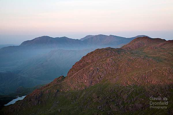 pavey ark, stickle tarn and the coniston fells bathed in red predawn light