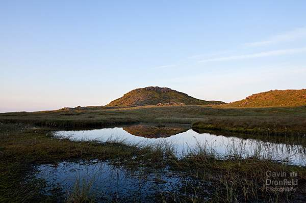 reflections of sergeant man summit crag in a calm tarn during clear dawn
