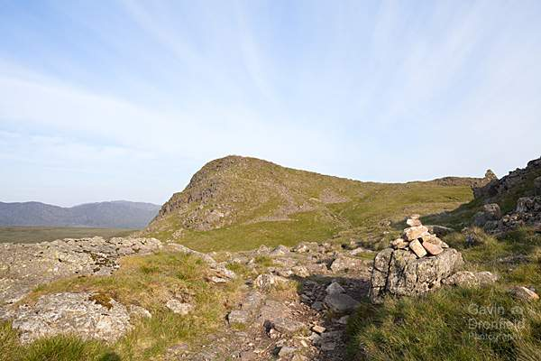 sergeant man crag summit from easedale footpath under blue skies with cirrus clouds