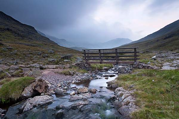 wooden footbridge over styhead gill with dark moody clouds shrouding the fells