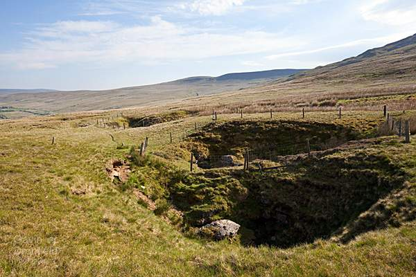 angerholme pots sinkholes lining the path across mallerstang common with Swarth Fell on the skyline