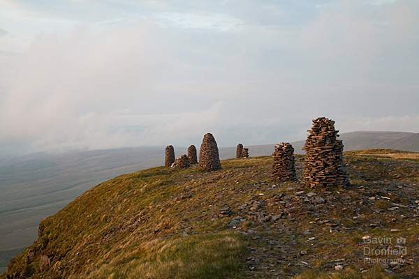 stone men cairns on wild boar fell during cloudy dawn
