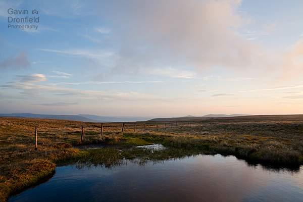 unnamed tarn and fence on wild boar fell with distant howgill fells at sunset
