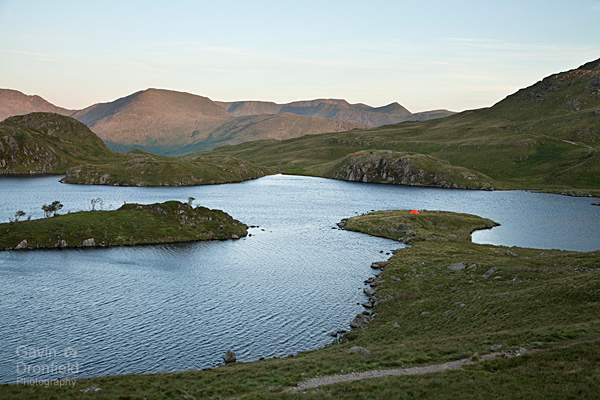 tents on the shore of angle tarn with backdrop of helvellyn at dawn