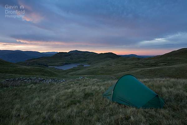 tent pitched under brock crags with view of angle tarn and angletarn pikes under colourful cloudy sunset skies