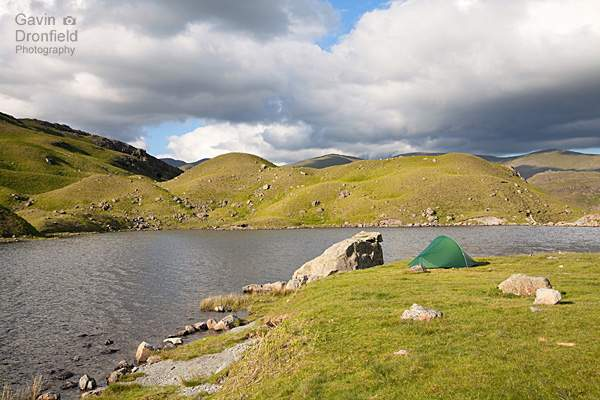 terra nova tent pitched on grassy area beside easedale tarn under fluffy clouds