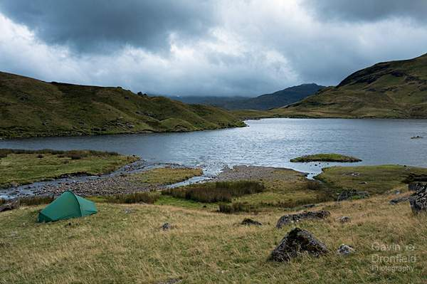 stickle tarn under stormy skies at sunset with a tent on the tarn shore