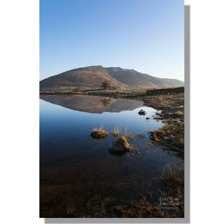 Blencathra perfectly reflected in Tewet Tarn at dawn under clear blue skies