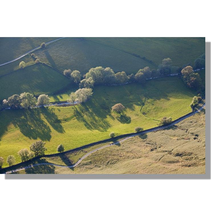 newlands beck meanders through green summer fields at sunset