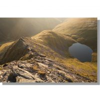 Sun rays at dawn looking down Sharp Edge to Scales Tarn on Blencathra
