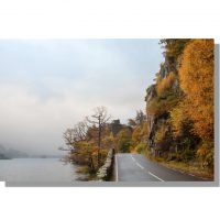 A592 Glenridding Road passes under autumnal Stybarrow Crag