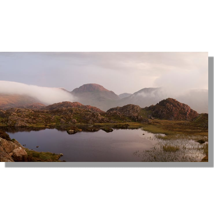 Innominate Tarn view towards red tinged Great Gable during atmospheric stormy sunset