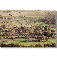 west burton in bishopdale surrounded by autumnal woodland under burton moor