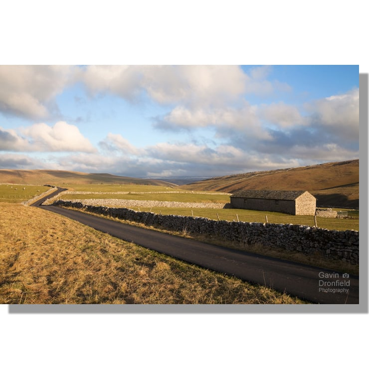 minor lane over malham moor to darnbrook house in winter sunset