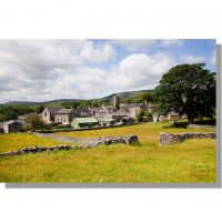 Askrigg village across blooming yellow wildflower meadows