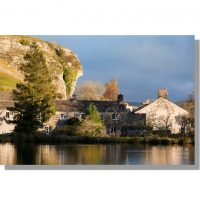 kilnsey crag above kilnsey village reflected in kilnsey park pond