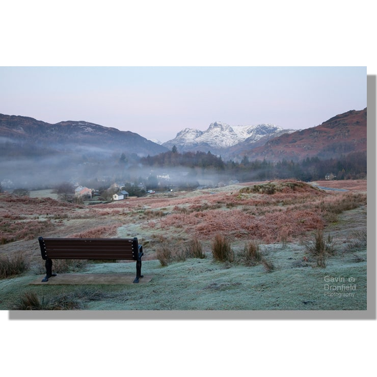 frosty elterwater common bench view of langdale pikes under pre-dawn pink sky