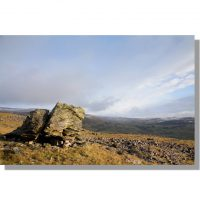 norber erratic boulder in sunshine under cloudy wintery skies