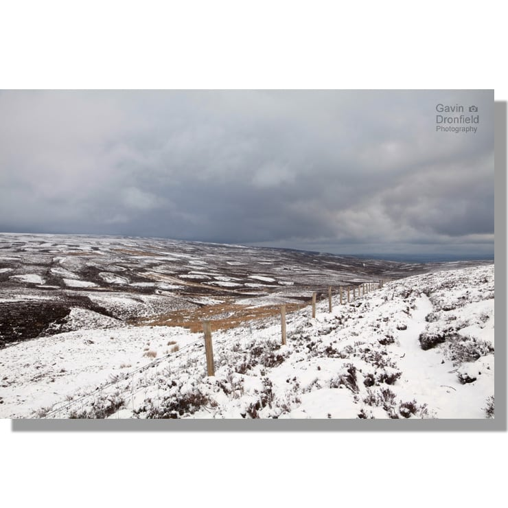 beldon beck valley on a snowy west bolton moor under ominous skies