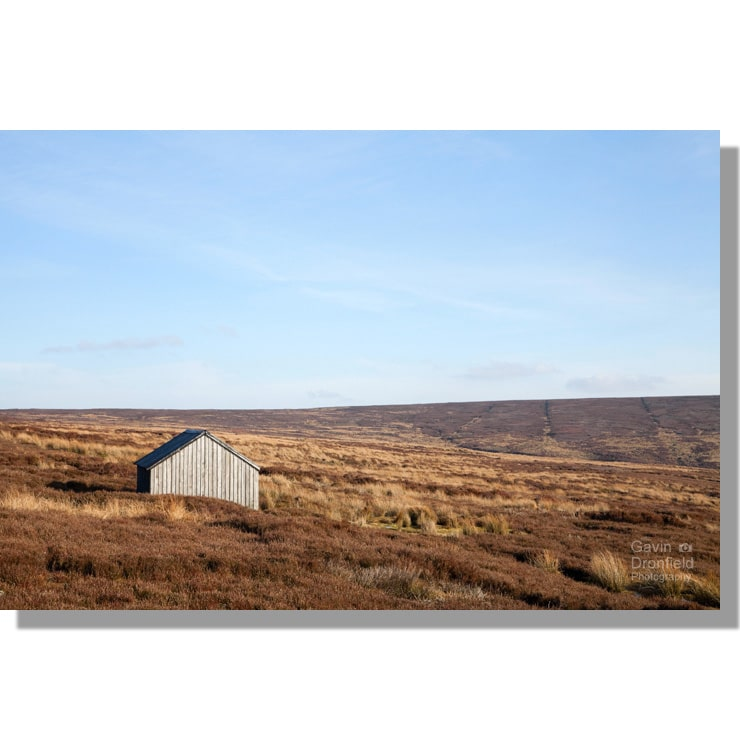 wooden shooting hut on slape wath moor on winter moorland under blue skies