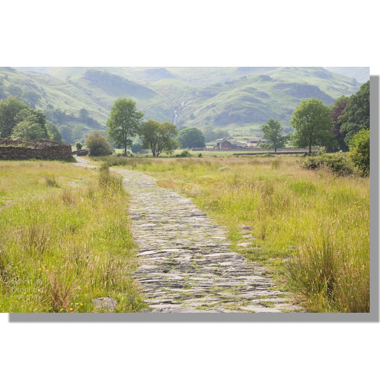 paved easedale path through summer meadows leading to new bridge and sour milk ghyll
