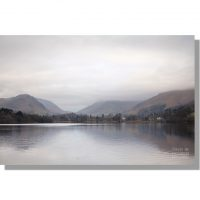 grasmere lake calm winter reflections of helm crag and dunmail raise under grey cloudy sky