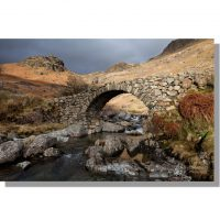 ancient stone packhorse bridge of lingcove bridge over lingcove beck surrounded by winter hues