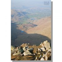 little langdale tarn and greenburn reservoir from craggy summit of great carrs on warm hazy spring day