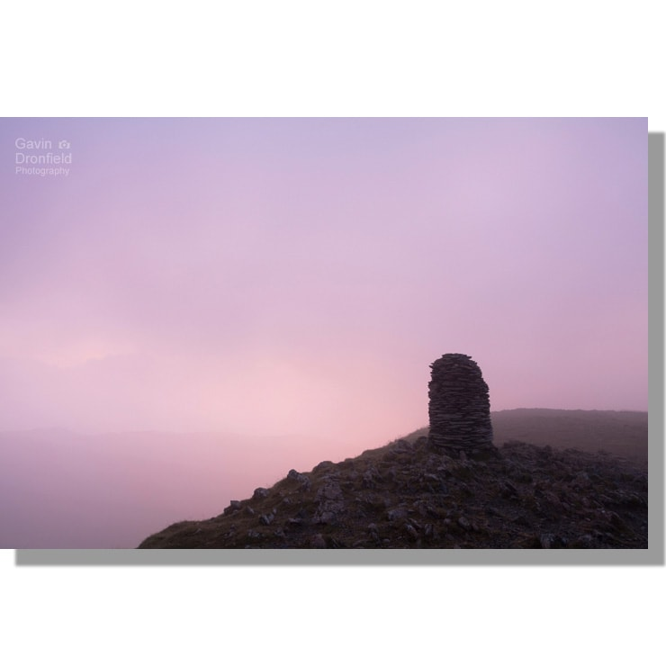 atmospheric pink tinged cloud swirling round silhouetted trig point on dale head at dawn