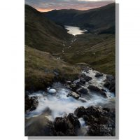 small water beck tumbles over a waterfall flowing towards distant haweswater reservoir under red dawn skies