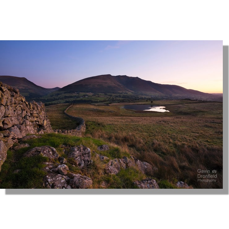 colourful red blue dawn sky over tewet tarn and blencathra from dry stone wall on low rigg