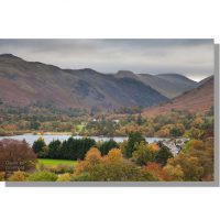 colourful autumnal trees concealing glenridding and patterdale with brock crag in background under leaden skies