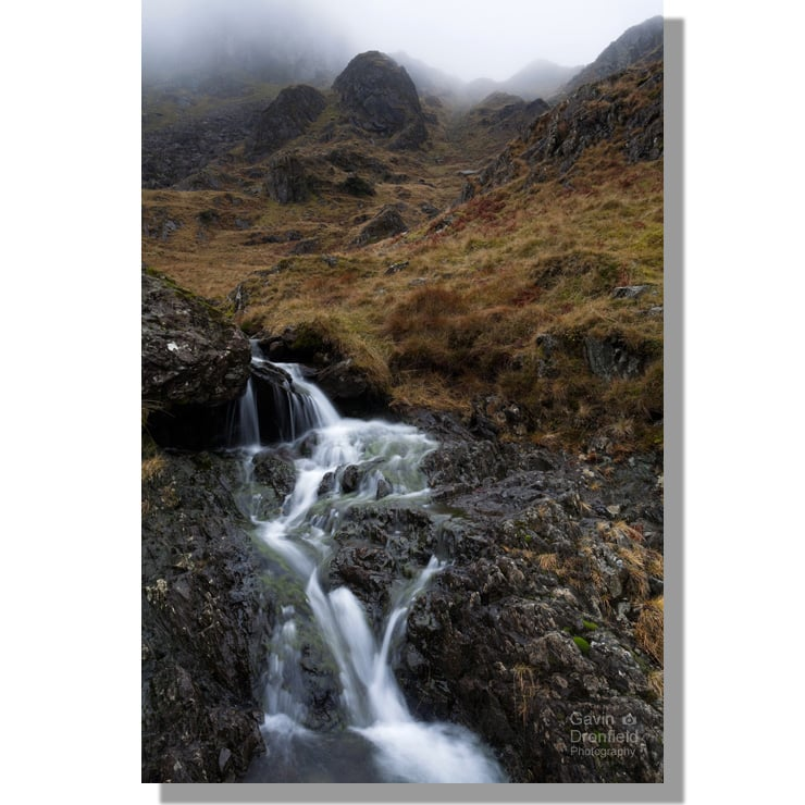 waterfall in dovedale beck under atmospheric cloud enshrouded summit of dove crag