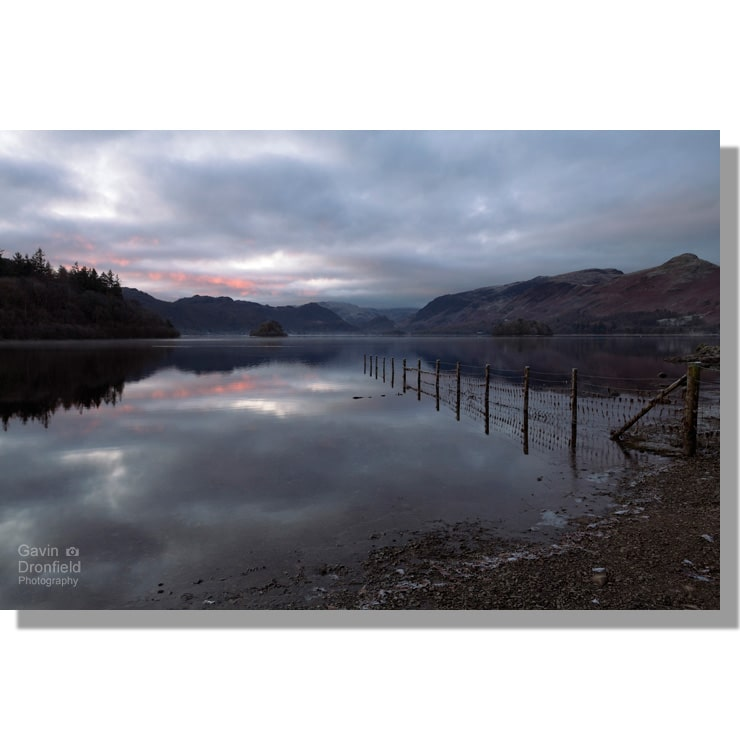strandshag bay view of red tinged cloudy dawn over calm derwent water and catbells